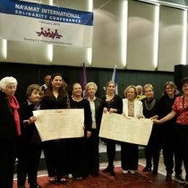 """Past presidents of NA'AMAT Israel Tamar Eshel, Masha Lubelsky, Talia Livni and Ofra Friedman join Galia Wolloch, current president of NA'AMAT Israel, Elizabeth Raider, president, NA'AMAT USA, and presidents from other NA'AMAT countries display signed """"Declaration of Solidarity and Support for the State of Israel and NA'AMAT."""""""